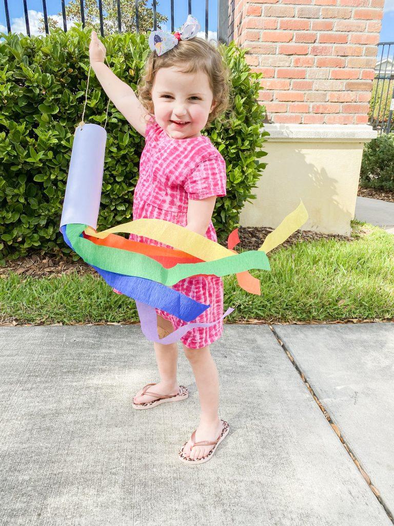 Caroline with Rainbow Windsock outside