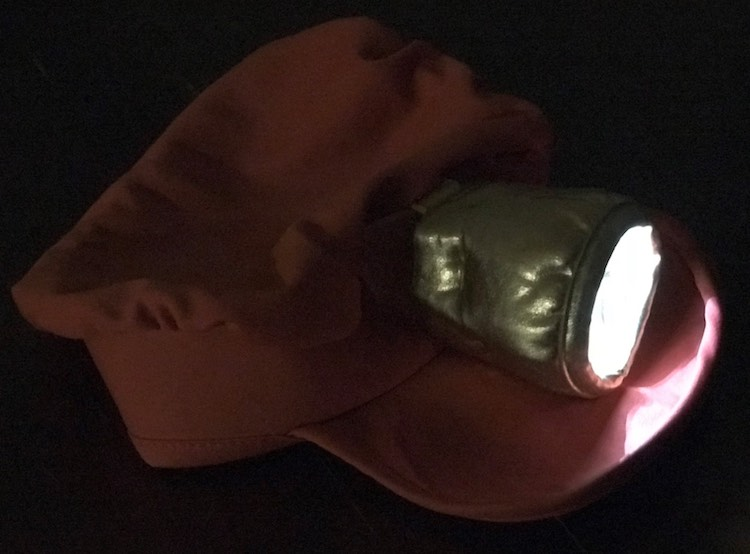 Finished hat with light on in the dark.