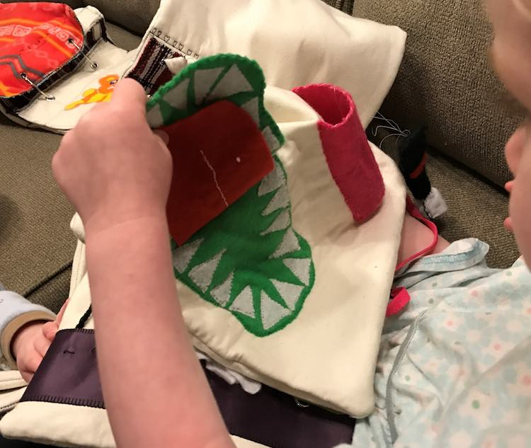 Toddler playing with her crocodile page.