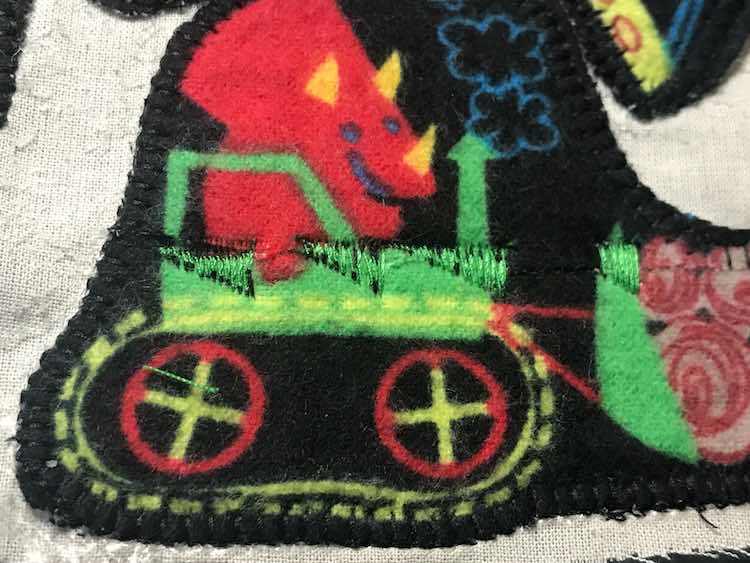 So I used green thread to stitch across the line being careful to not go over the black or the dinosaur's hand.