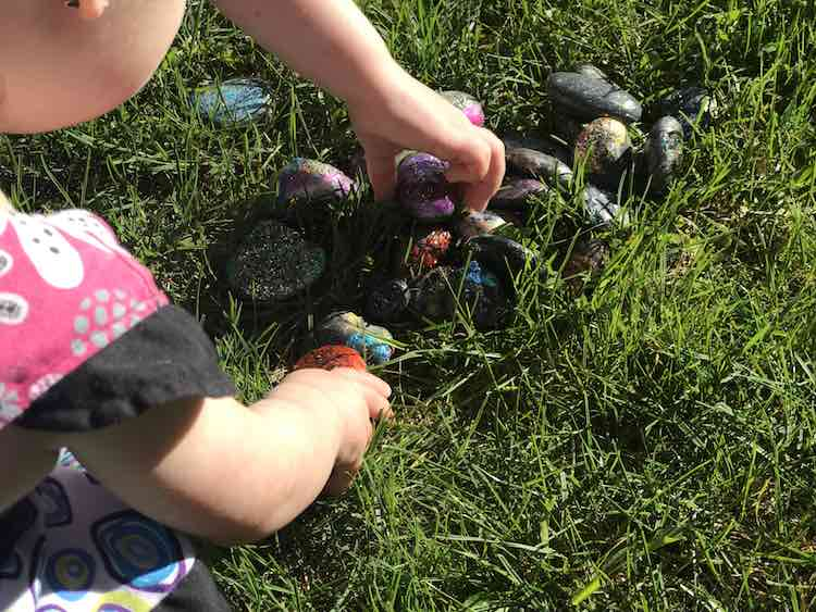 The painted rocks nestled in green grass. Both girls are leaned over picking their favorites.