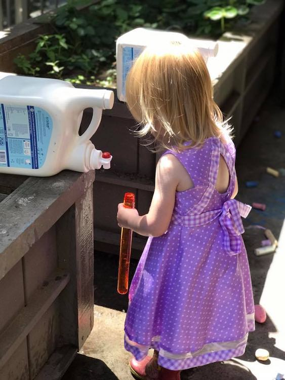 Here Ada used an emptied bubble wand container to hold, transport, and dump the water.