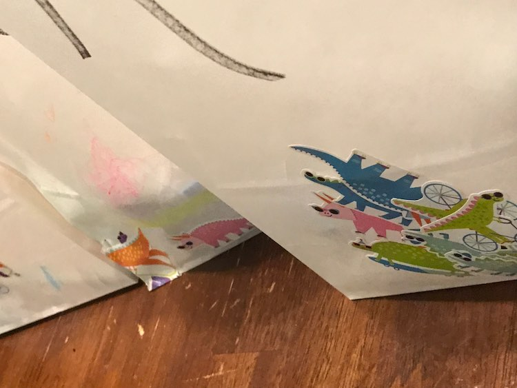 I bought a large package of white paper bags so Ada could decorate them. I went through and wrote all the names of the guests on them and then passed them in sets of one or two to Ada to decorate with crayons (ignored) and stickers.