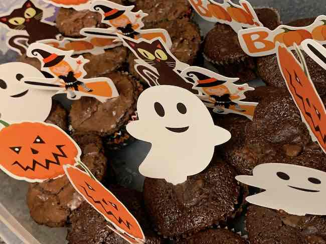 After they cooled I put most of them (that would fit) in a large plastic container and added Halloween themed cupcake toppers.