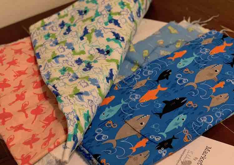 The outer and lining comes in two pieces so the kids got to pick two fabrics each so half would be one and the other half the other. Zoey went with ballet and dinosaur fabric while Ada choose sleepy dinosaurs and sharks. All fabrics had been bought from JOANN Fabrics with three of them thin fuzzy flannel and the sharks with no fuzz.