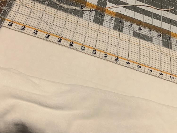 I started by folding my backer in half to better fit on my cutting mat. After squaring and trimming the edge I then used my acrylic ruler and set it up four inches in from the edge so I could easily cut my strip. I did this one more time to get my second strip.