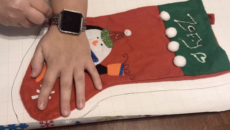 I held two pens while tracing around the stocking. The one pen drew while the other pen was used as a spacer so the line would be further away from the stocking. I wanted a slightly larger stocking and wasn't sure how much space I'd need for seam allowance.
