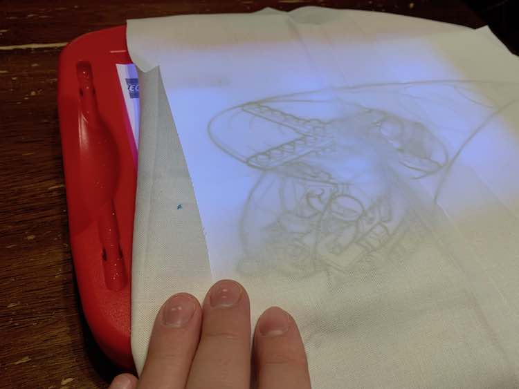 Coloring page and fabric overtop of a light box so tracing would be easier.