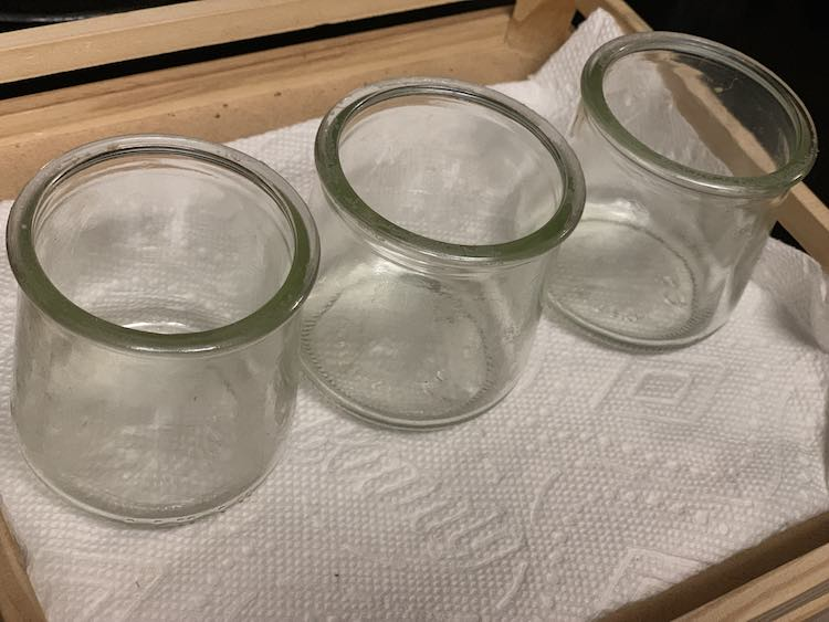 Three identical jars lined up on a paper towel lined tray.