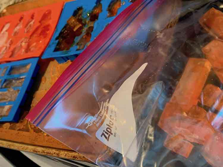 Foreground Ziploc freezer bag with a cookie sheet containing the other three silicone moulds filled with orange dyed ice in the background.