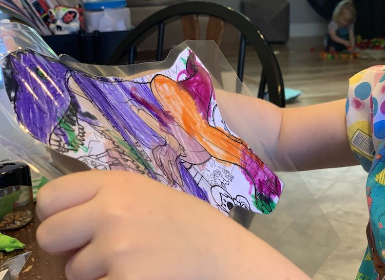 Foreground of the LEGO® dinosaur coloring page getting cut out and in the background Zoey crouched and playing with the DUPLO®.
