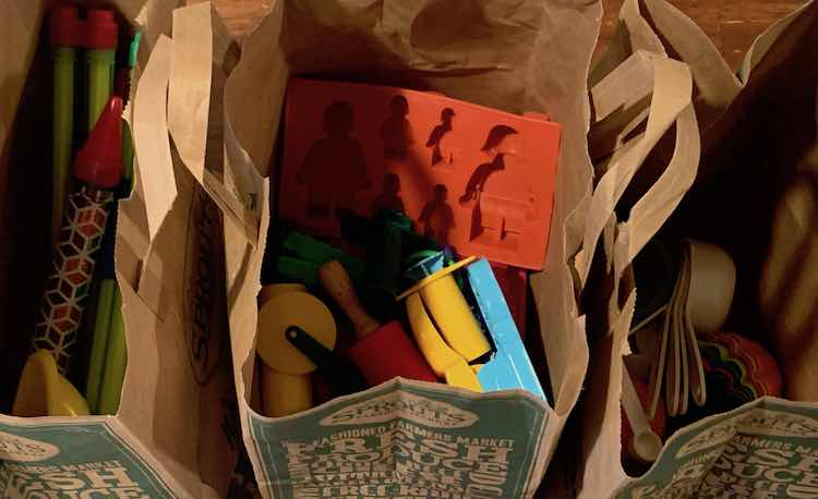Three paper bags side by side with sensory tools in them.