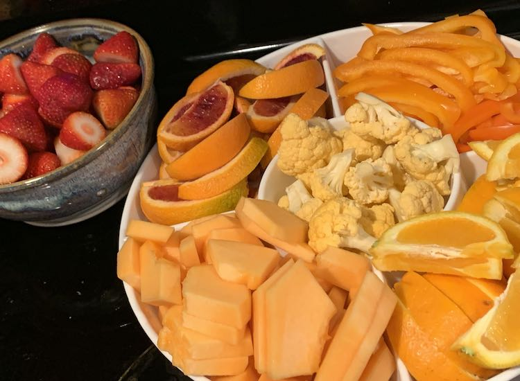 Mostly orange themed fruits and veggies. Tray holds the orange and there's a bowl of red strawberries in the back.