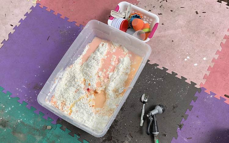 All the ingredients added to the bin (cornstarch, food dye, and water). The cornstarch is rising out from orange/pink water.