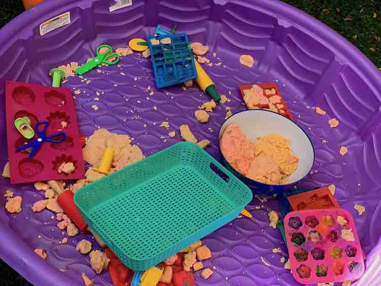 Dry pool filled with playdough bits and playdough tools.