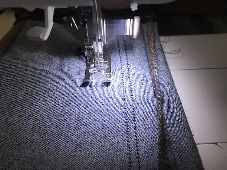 Sewing along the pant leg making sure to keep the stitches evenly apart from the previous row of stitches.