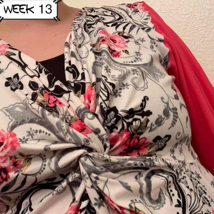 Closeup of another Mariella top. This one has white fabric with pink flowers and vines in black and grey over it. The arm showing in the back of the image is made of pink fabric.