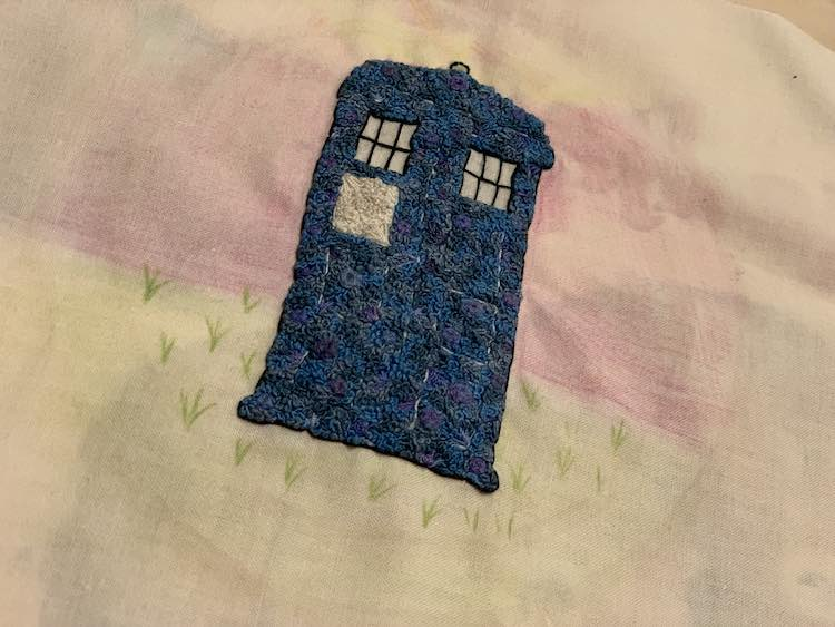 TARDIS with a mostly flatly colored background and some grass lines in the ground.