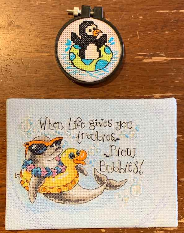 """The two finished and mounted embroidery kits. The smaller circled one (penguin floating in an inner tub) above the dolphin in an inner tube with quote: """"When Life give you troubles... ... Blow bubbles!"""""""