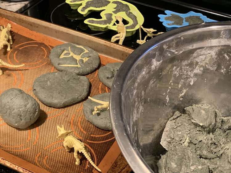 Bowl of unused grey salt dough in the foreground with fossil imprinted rocks forming themselves in the background. Behind all of that you can see the dinosaur skeleton moulds filled with grey salt dough.