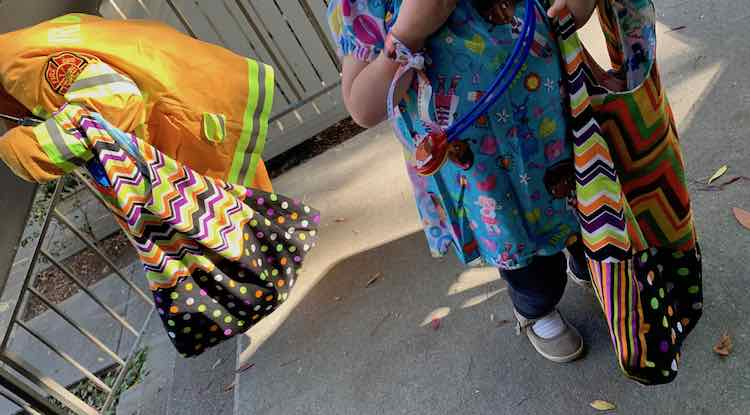 Ada in her firefighter costume carrying her halloween bag on the left and Zoey facing the camera on the right. She's wearing a Doc McStuffins top, carrying her Halloween bag, and is wearing a Doc McStuffins ribbon around her wrist while having a stethoscope around her neck.