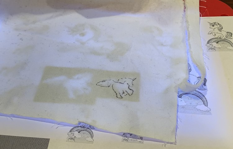 White woven fabric with a running unicorn partly traced. The fabric is draped over a piece of printed paper and a kids' light box.