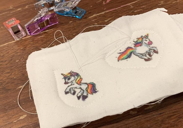 A swatch of fabric with two unicorns colored on. The left unicorn has a tear drop sewn around it while the right most unicorn has a heart. Both shapes have the threads left untrimmed at this point.