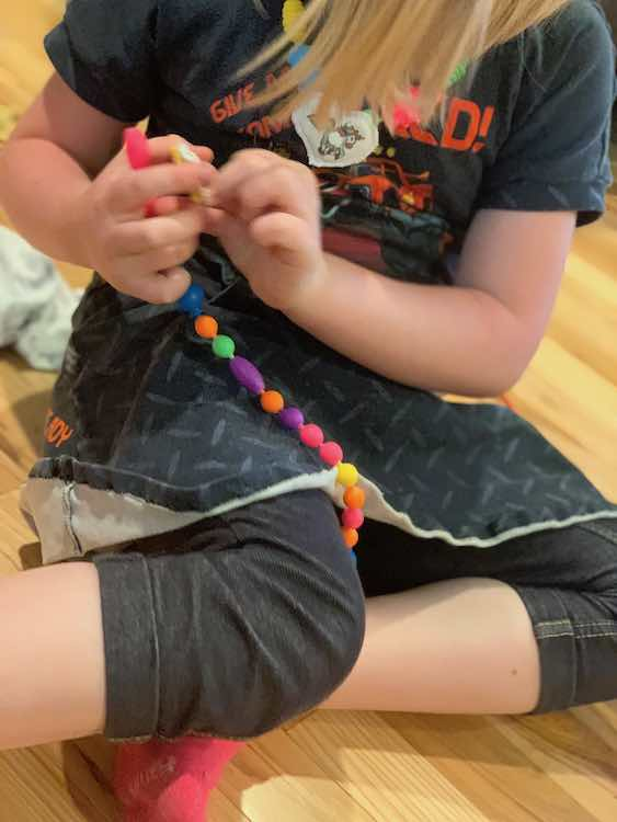 Ada sitting down and about to add the other pendant to a newly made strand of pop snap beads.