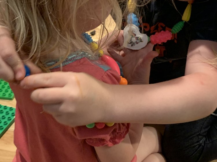 Ada putting Zoey's new necklace on her while Zoey examines Ada's unicorn on her necklace.