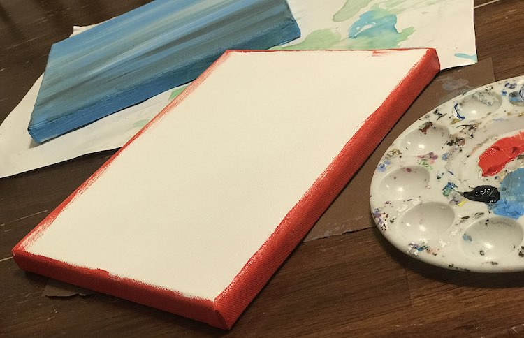 The finished blue canvas sits in the background and the paint palette with the four colors on it sits near the front partially off screen. Between the two is the second white canvas with all four sides painted red.