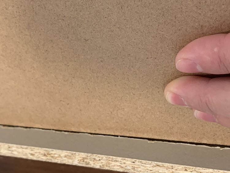 Closeup of the center of the upside down drawer. You can see my fingers (to the right) holding down the drawer base. Since the base is shoved into place you can see the groove where the drawer base used to sit inside.