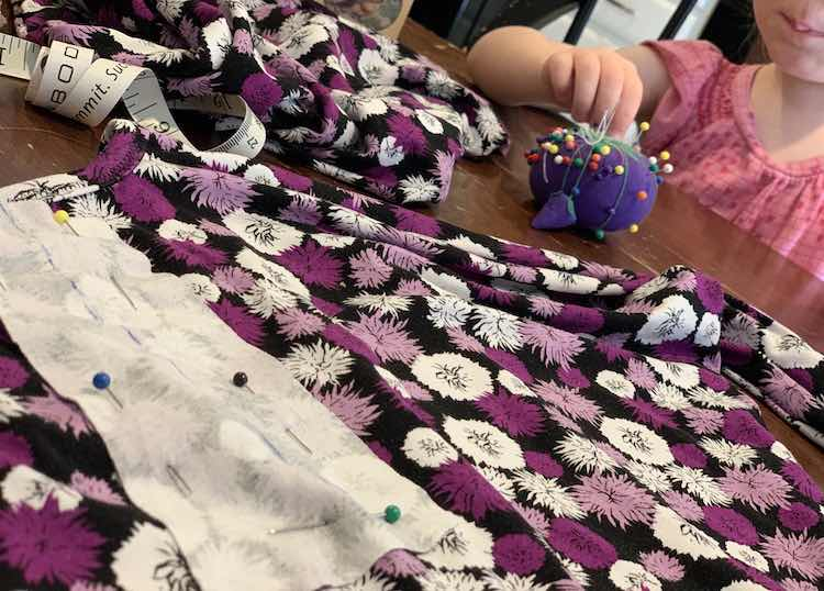 Foreground shows the shirt on the table with the placket pinned in place on it. Since the fabrics are right sides together you can easily see the sketched on line on the placket facing. In the background Zoey is pulling a pin into or out of my purple pin tomato.