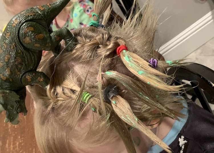 Side view of the hair shows the dinosaur who appears to be roaring. You have a view of the green flecked hair pointed away from Ada's head and the individual 'grass' at the back.