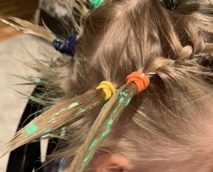 Side view of Ada's hair showing two ponytails in the foreground. Both ponies (orange tie from a braid with a yellow ponytail tie behind) end with a spike of hair pointed away from Ada's head and are dappled with green spots. In the background you can see the back of Ada's short hairs spiked up and a couple other ponytails.