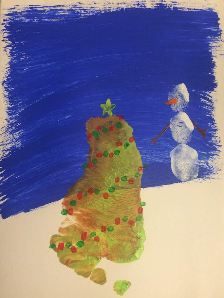 Closeup of a Christmas card showing a footprint tree adorned with angled rows of green and red dots and a yellow star sitting at the top. The snowman to the right had brown twig arms and a yellow triangle nose.