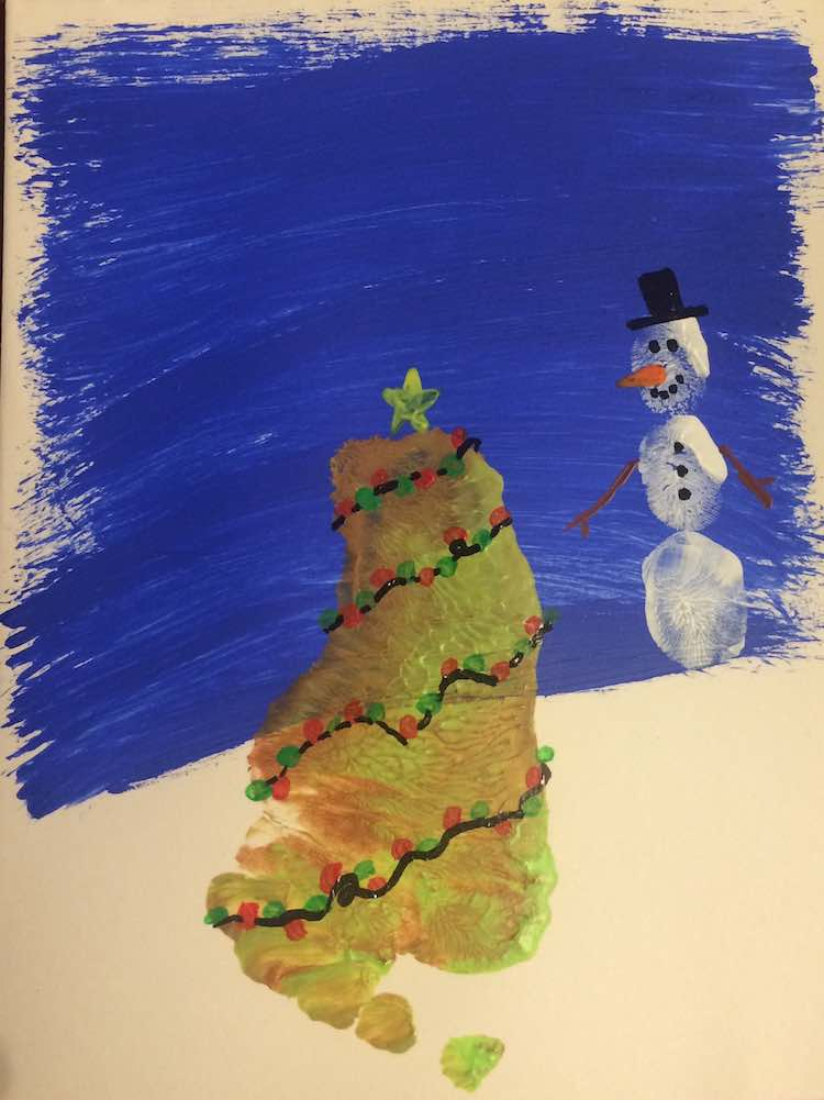 Finished Christmas tree and snowman. The tree has a yellow star at the top and is surrounded by a string of red and green Christmas lights. The snowman has a top hat, twig arms, carrot nose, coal face, and coal buttons.