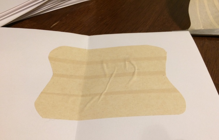 Opened card with a curved square shape of masking tape stuck to the inside.