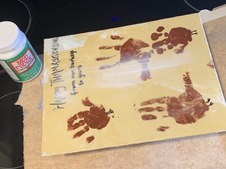 Top sideways view of the Thanksgiving canvas. There are vertical streaks of white near the center and the rest is clean allowing you to see the painting below.