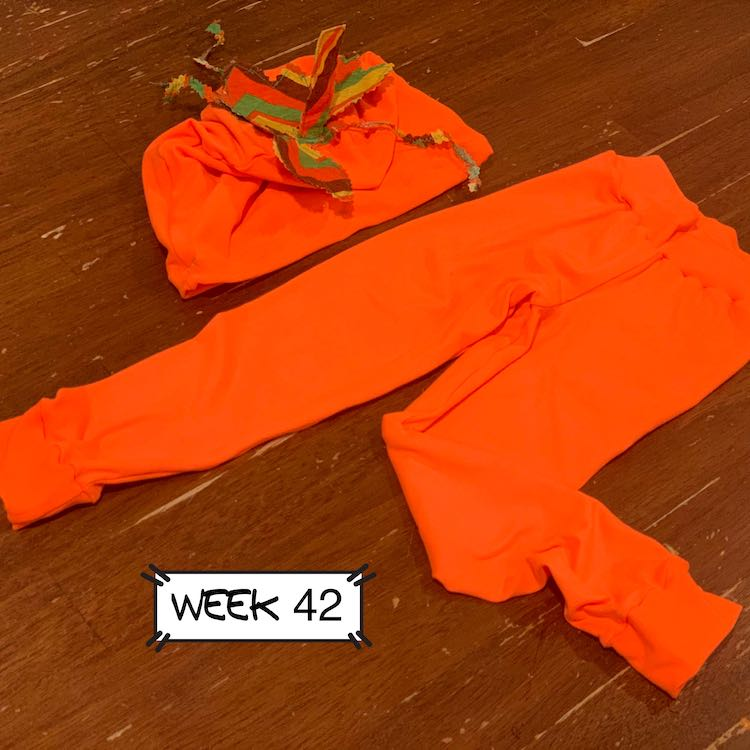 A neon orange beanie with striped leaves laying on a table next to neon orange leggings. The leaves are striped brown, orange, green, and yellow.