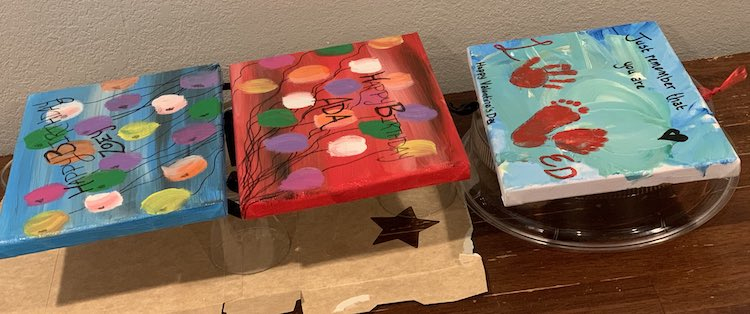 The two Happy Birthday signs are propped up on glass cups on an opened cardboard box, like before, while the Valentine's Day loved sign is on a microwave dish cover to the right.