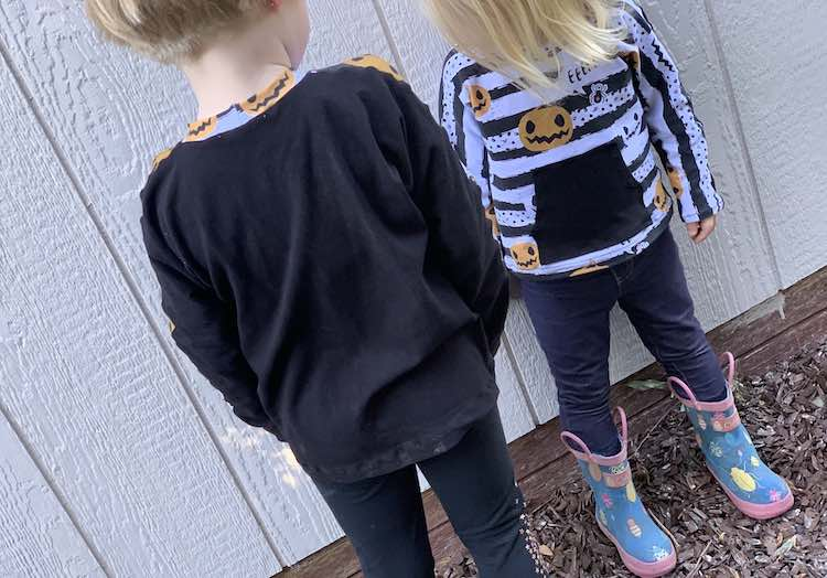 Ada is slightly closer to the camera facing Zoey so Ada's back is to you and Zoey's front is facing you. You can see the back of Ada's top showing the pumpkins on the back of her neckband. Zoey's hair is obscuring the top of her top.
