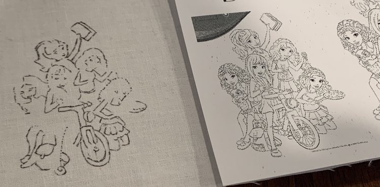 Closeup of two images showing the LEGO® Friends. The image on the right is part of the printed out coloring page. The image to the left shows a partial drawing using black ink on white woven fabric.