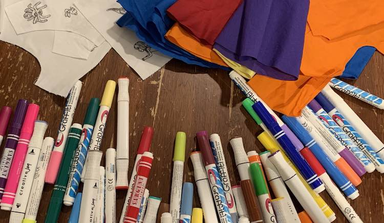 The image shows varying hues of fabric markers spread across the table and along the bottom of the image. The upper half of the image shows the stacked bodice pieces, to the left, and the pile of cut, presewn, skirt pieces to the right and overlapping the pattern pieces and some of the markers.