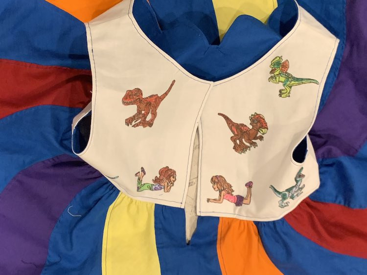 The back of the bodice is, mostly, visible showing the two laying down LEGO® Friends and four of the five dinosaurs. The skirt swirls are radiating out from the bodice.