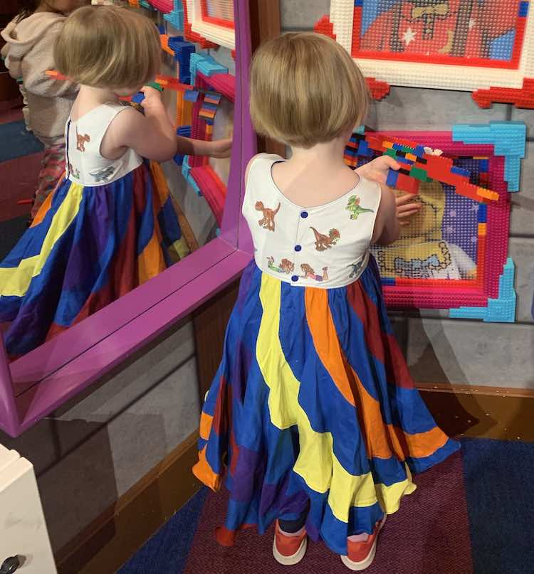 The back of Ada is shown as she holds her LEGO® structure and touches a LEGO® picture brick frame while standing beside a mirror.