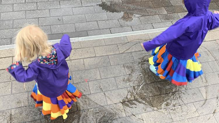 Photo is taken from above looking down at the girls' backs while they stand in puddles wearing rain jackets.