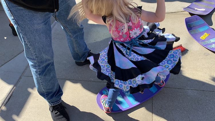 Photo taken looking down at Zoey on a balance board. She's holding her dad's hand, on photo, and getting twirled.