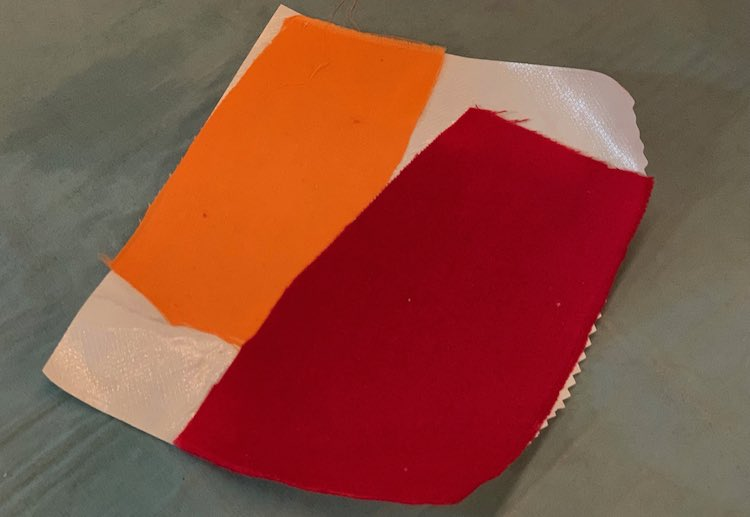 Photo showing two rectangular scraps of fabric, one orange and one red, attached to the shiny side of heat'n bond interfacing,