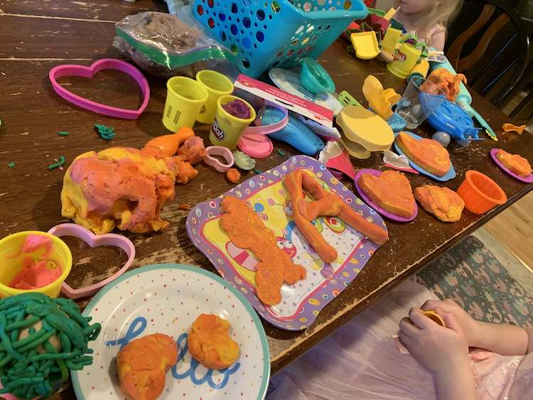 Playdough cookies plated on many different plastic plates and a tea tray. The plates, playdough, and tools are spread across the table while both kids sit at the table creating.