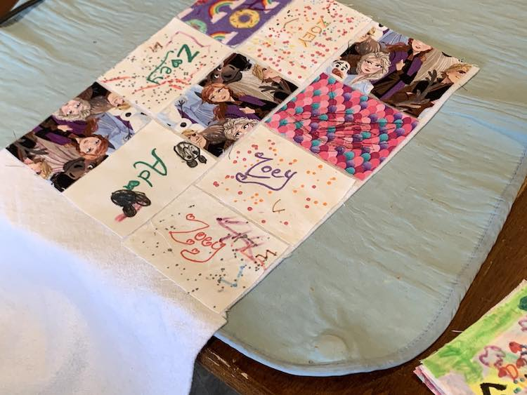 Showing ten of the sixteen rectangles laid out on the fusible fleece leaving a small border around each one. The bottom right side of the photo shows the remaining pile of rectangles that still needed to be laid out.